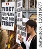 AMSTERDAM, NETHERLANDS - AUGUST 8: A young woman praying while a demonstration against chinese invasion of Tibet on August 8, 2012 in Dam Square, Amsterdam. About 100 people joined this demonstration. - stock photo