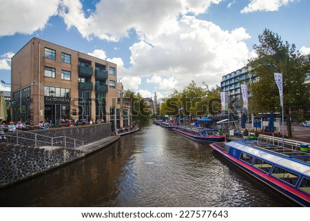 AMSTERDAM - NETHERLANDS: AUGUST 11, 2014: Tourist city sightseeing boats in the canal next to Aran pub. - stock photo