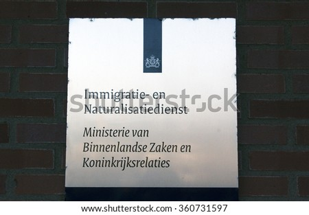 Amsterdam, Netherlands-januari 8, 2016: sign of the Immigration and Naturalization Service of the Ministry of the Interior and Kingdom Relations - stock photo