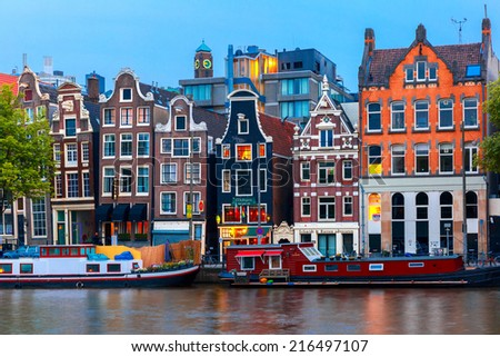 Amsterdam, Netherlands - July 30, 2014: Night city view of Amsterdam canal, typical dutch houses and boats, Holland. Canal ring area placed on the UNESCO World Heritage List. - stock photo