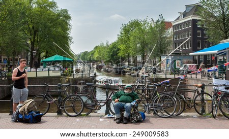 AMSTERDAM, NETHERLANDS - JULY 13: The canal houses of Amsterdam on July 13, 2013. Amsterdam is the capital city and most populous city of the Kingdom of the Netherlands. - stock photo