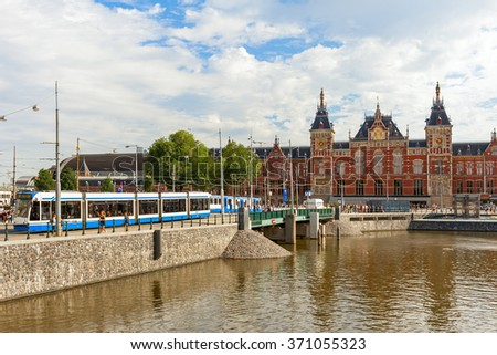 AMSTERDAM, NETHERLANDS - JULY 07, 2015: View of urban tram and Centraal - largest train station of Amsterdam, major national railway hub, designed by Dutch architect Pierre Cuypers and opened in 1889. - stock photo