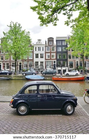 AMSTERDAM, NETHERLANDS -10 JUNE 2015- A vintage Fiat 500 car is parked on the street along a canal in Amsterdam. The Cinquecento was produced by Fiat between 1957 and 1975. - stock photo