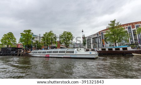 AMSTERDAM, NETHERLANDS - MARCH 14, 2016: A sightseeing tour boat in a canal in amsterdam, Netherlands. Amsterdam Canal Cruises are one of the best ways to enjoy the city in a short time. - stock photo
