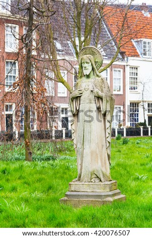 Amsterdam, Netherlands - March 31, 2016: Begijnhof courtyard with Jesus statue and garden surrounded by historic houses in Amsterdam, Netherlands - stock photo
