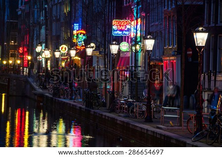 AMSTERDAM, NETHERLANDS - MARCH 16, 2014: Night view of Red - light district, where is a concentration of sex shops, strip clubs, adult theaters, etc. The sign of Red Light Bar coffee shop - stock photo