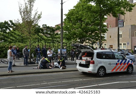 Amsterdam, Netherlands - May 21, 2016: Distant view of an injured cyclist lying on the ground after being hit by a car, surrounded by pass byers, two police officers and a police car. - stock photo