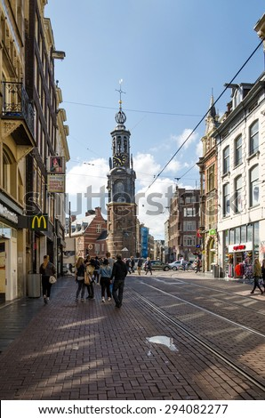 Amsterdam, Netherlands - May 8, 2015: People at The Munttoren (Mint Tower) Muntplein square in Amsterdam, This tower was once part of one of the three main medieval city gates.  - stock photo