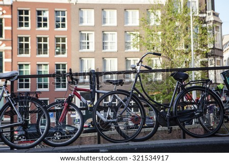AMSTERDAM, NETHERLANDS - MAY 13, 2015: Typical bicycles, the most popular transportation system in Netherlands, parked on Amsterdam bank canal - stock photo