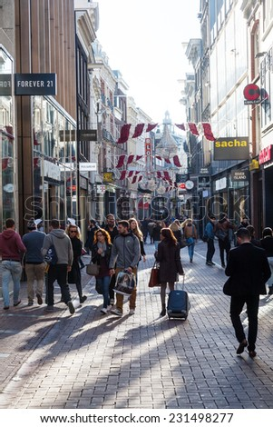 AMSTERDAM, NETHERLANDS - NOVEMBER 13: Kalverstraat with unidentified people on November 13, 2014 in Amsterdam. It is a busy shopping street and the most expensive one in the Netherlands - stock photo