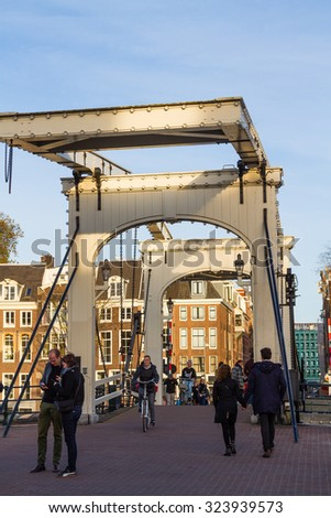 AMSTERDAM, NETHERLANDS - NOVEMBER 10: Old drawbridge with unidentified people on November 10, 2014 in Amsterdam. It is the capital of Netherlands with more than 3.66 mio international visitors a year - stock photo