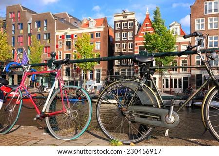 AMSTERDAM, NETHERLANDS,OCTOBER,07: Color bicycles parked at Amsterdam canal street of traditional dutch colorful buildings. Amsterdam - the bicycle capital of Europe, on October 07, 2014, Netherlands - stock photo