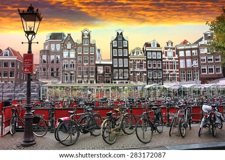 AMSTERDAM,NETHERLANDS,OCTOBER, 06, 2014: Sunset in Amsterdam.Bicycle parking and traditional old dutch buildings.Flower market on Single canal, Netherlands. Amsterdam is the bicycle capital of Europe  - stock photo