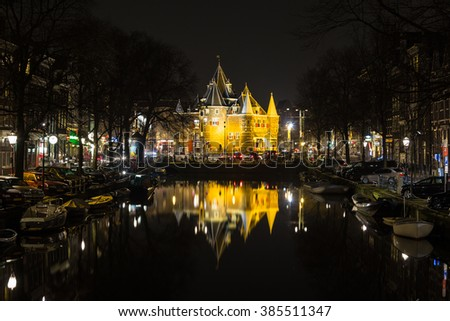 """AMSTERDAM, NETHERLANDS - 16TH FEBRUARY 2016: A view towards The Waag (""""weigh house"""")  in Amsterdam from the Kloveniersburgwal canal at night. Cars, bikes and other buildings can be seen. - stock photo"""