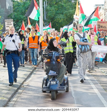 AMSTERDAM, THE NETHERLANDS - AUGUST 3, 2014: Participants of the Pro-Gaza demonstration march in the streets of the city protesting against violence in Gaza region - stock photo