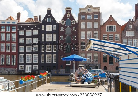 AMSTERDAM,THE NETHERLANDS - July 30, 2014: Houses on the banks of the canals of Amsterdam. Houses in Amsterdam are located directly on the water. Popular tourist attractions. - stock photo