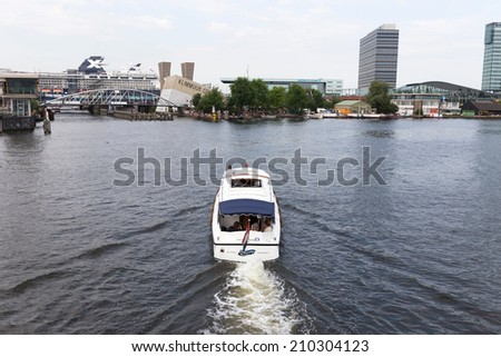 AMSTERDAM, THE NETHERLANDS - July 31 2014: View of boat from Mr. JJ van der Veldebrug - bridge towards bay in Amsterdam, Netherlands. The place includes a museum, science labs and other attractions. - stock photo