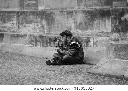 Amsterdam, The Netherlands - May 9, 2015: old poor  man sitting and smoking  near Amsterdam Palace,  in  Amsterdam on May 9, 2015 in Amsterdam, Holland - stock photo