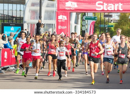 AMSTERDAM, THE NETHERLANDS - OCTOBER 25, 2015: Participants of Ajax Run start a 5 km race. Ajax Run is a public non-ticketed running event for recreational athletes, held in the city's streets - stock photo