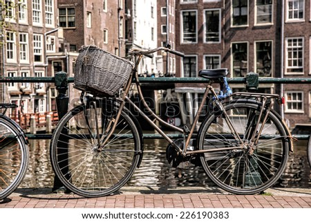 Amsterdam with old bicycle on the bridge against canal in  Holland - stock photo