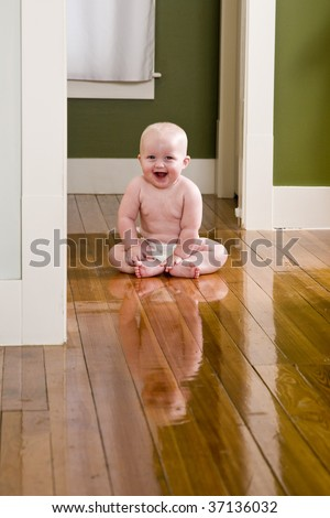 Amused baby sitting on floor wearing diaper - stock photo