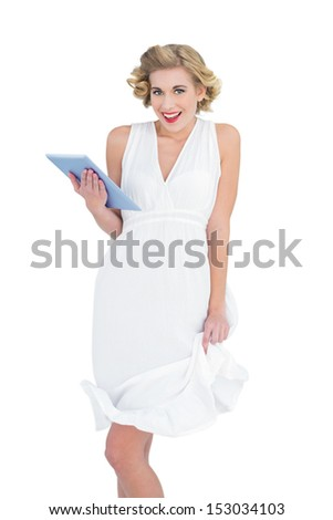 Amused fashion blonde model holding a tablet pc on white background - stock photo