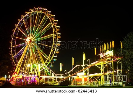 Amusement park at night - ferris wheel and rollercoaster - stock photo