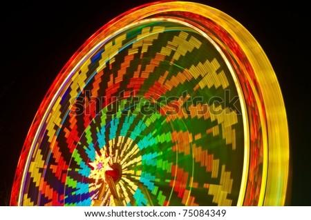 Amusement park at night - ferris wheel  in motion - stock photo