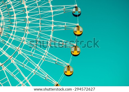 Amusement park ferris wheel in the blue sky - stock photo