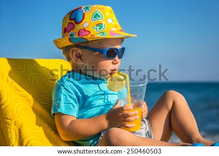 Amusing kid drinks juice from tubule against sea in sunny day - stock photo