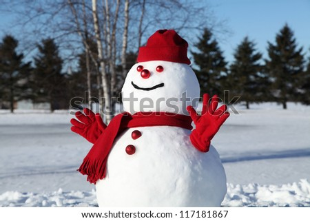 Amusing snowman in red on a beautiful and cold winter morning - stock photo