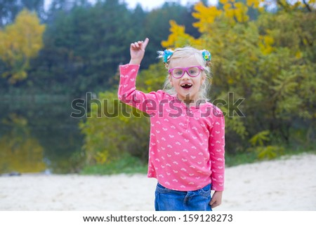 Amusing wriggling girl in pink glasses outdoors - stock photo