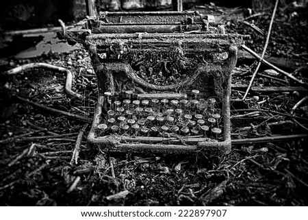 An abandoned and broken, antique, vintage typewriter, left outdoors with weeds and grass growing over it. In black and white. - stock photo