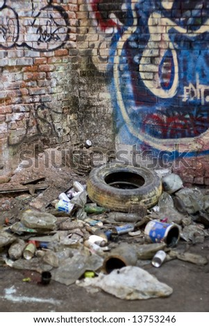 An abandoned area that is covered with trash and street graffiti.  This makes an excellent background or backdrop.  Shallow depth of field. - stock photo