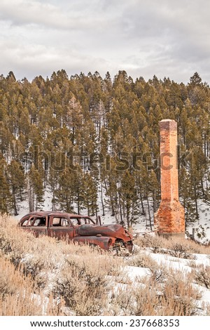 An abandoned automobile parked near a brick chimney in a Montana ghost town on a winter day - stock photo