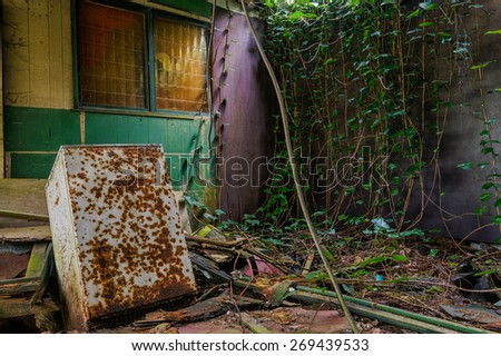 An abandoned fridge in an abandoned zoo. - stock photo