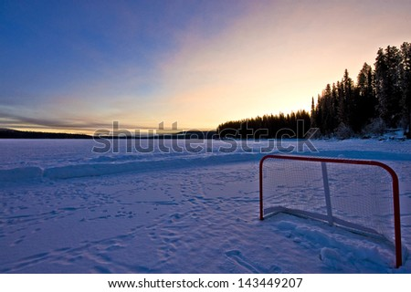 An abandoned hockey net on a snow covered, frozen lake in the early morning. - stock photo
