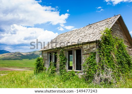 An abandoned weathered old farm house sits overlooking a fabulous view of the mountains in Idaho, near the Tetons and Yellowstone - stock photo