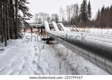 An above ground oi or gas pipeline in winter - stock photo