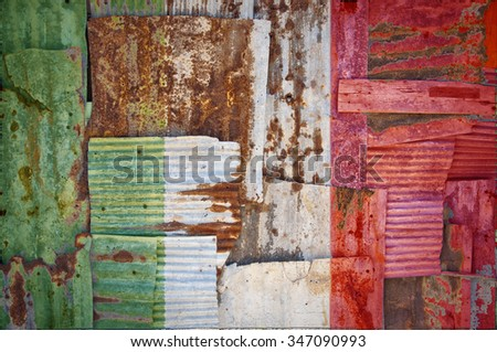 An abstract background image of the flag of Italy painted on to rusty corrugated iron sheets overlapping to form a wall or fence. - stock photo