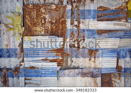 An abstract background image of the flag of Uruguay painted on to rusty corrugated iron sheets overlapping to form a wall or fence. - stock photo
