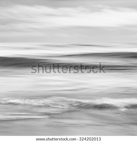 An abstract, black and white seascape featuring converging ocean waves.  Image made with panning motion and a long exposure for a soft, blurred effect. - stock photo