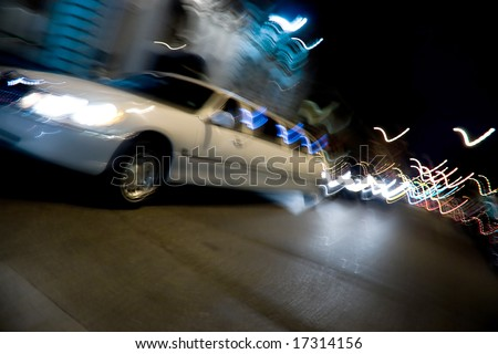 An abstract blur of a white limousine in the city at night with light trails. - stock photo