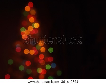 An abstract image featuring multi-colored light bokeh in the shape of a Christmas tree against a dark background.  - stock photo