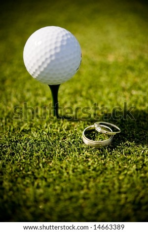 An abstract image of wedding rings lying next to a golf ball on a tee - stock photo