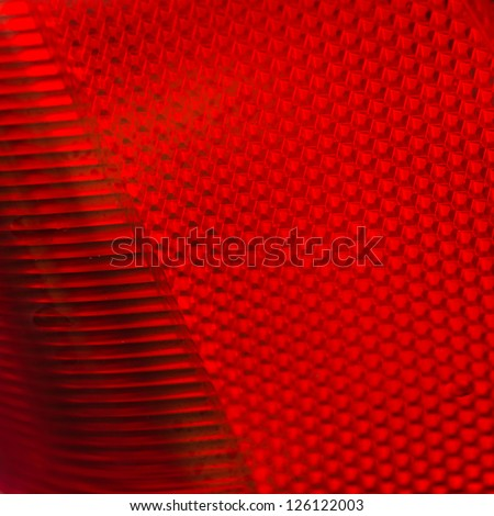 An abstract macro shot of a red car brake light. - stock photo