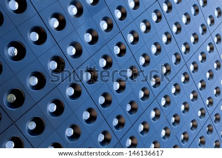 An abstract pattern of tiles with glass circles on the exterior of a building. - stock photo