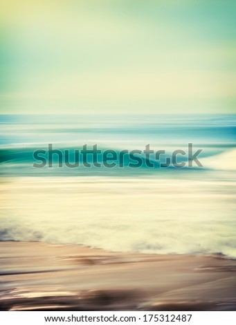 An abstract seascape with blurred panning motion combined with a long exposure.  Image displays a retro look with cross-processed colors.  There's a very fine grain texture visible at 100 percent. - stock photo