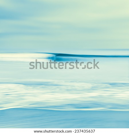 An abstract seascape with blurred panning motion.  Image displays blue and yellow cross-processed colors. - stock photo