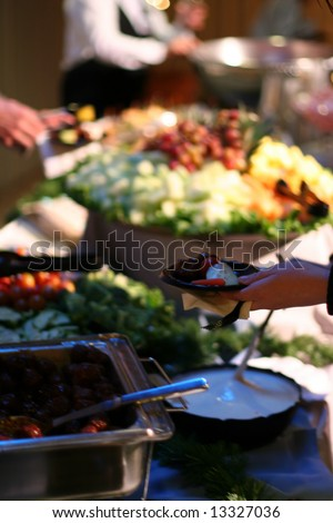 an abundance of food with people serving themselves - stock photo
